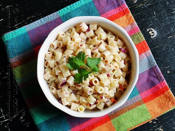 An overhead photo of pasta salad in a white bowl with parsley on top.