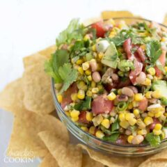 Cowboy Caviar is a popular potluck, BBQ, party and game day appetizer. Here we combine avocado, corn, black-eyed peas, Roma tomatoes, garlic, cilantro, green onions and a few other ingredients to make a tasty dip.