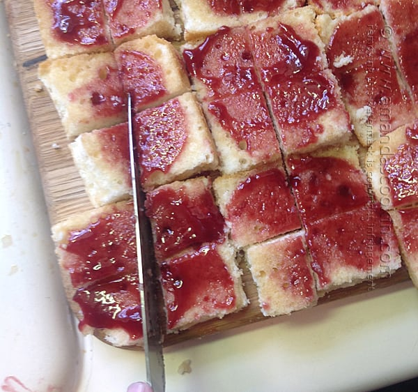 cut the jam covered sherry soaked cake into small squares