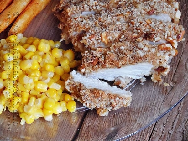 A close up photo of sliced pretzel chicken on a plate with corn.