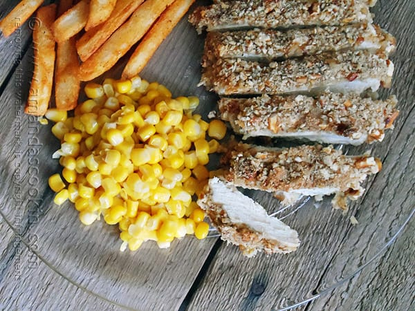 An overhead photo of sliced pretzel chicken on a plate with corn and fries.