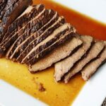A close up overhead of sliced slow cooker roast with brandy sauce on a white platter.
