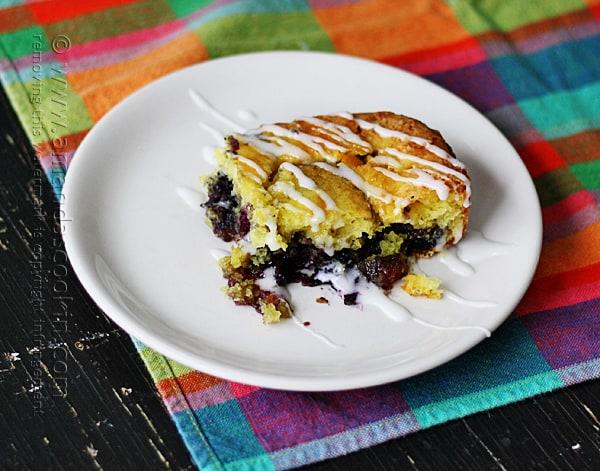 A close up photo of a piece of glazed lemon blueberry cake on a white plate.