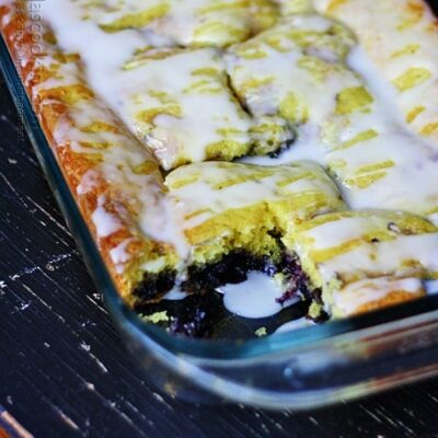 A close up photo of glazed lemon blueberry cake in a dish with a piece removed.