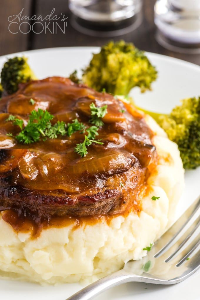 swiss steak and gravy on a pile of mashed potatoes