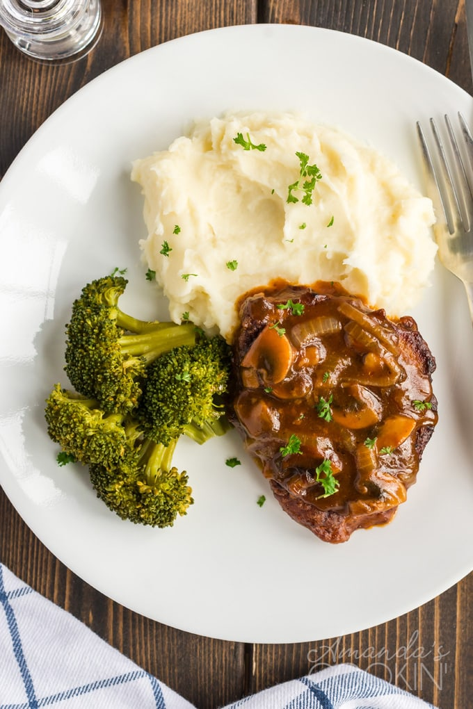 overhead photo of swiss steak on plate with mashed potatoes and broccoli