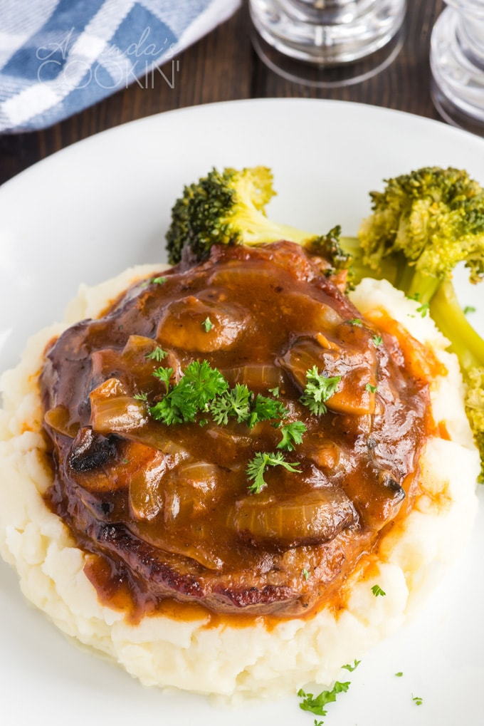 swiss steak in gravy on top of mashed potatoes