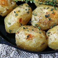 A close up photo of roast potatoes in a cast iron skillet.