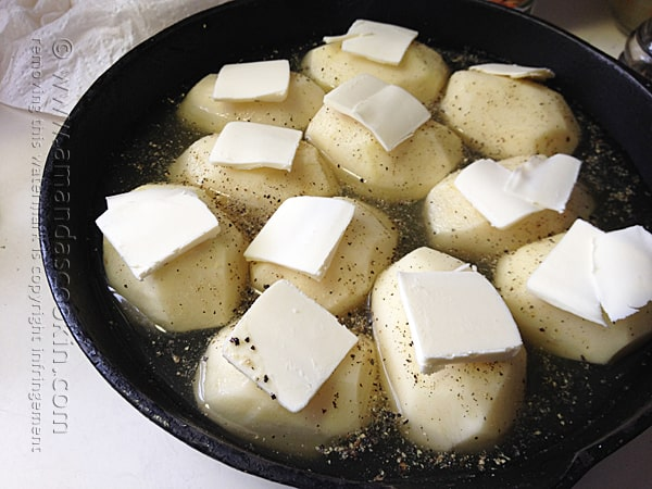 Add thinly sliced butter to the top of each potato before putting them in the oven