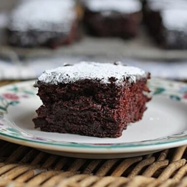 A close up of a square of wacky cake resting on a plate with powdered sugar on top.