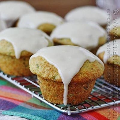 A close up photo of shortcut zucchini muffins resting on a cooling rack topped with sour cream glaze.