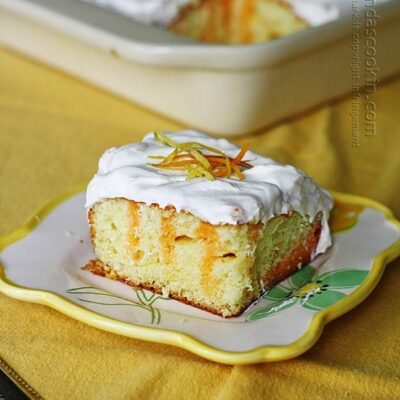A piece of citrus lover's poke cake on a square plate.