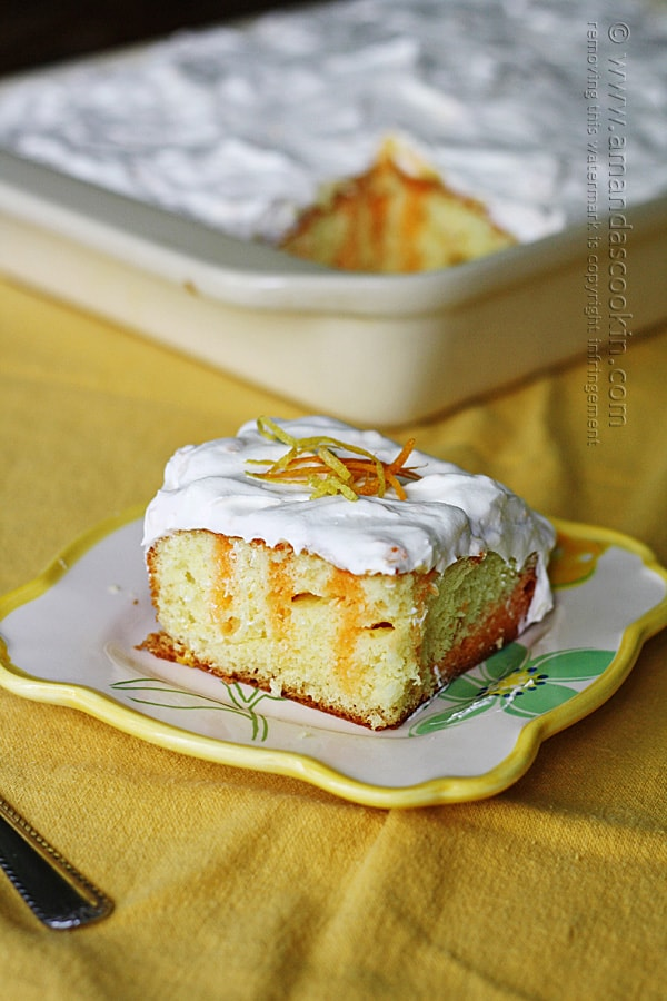 A piece of citrus lover\'s poke cake on a square plate.