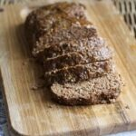 A photo of sliced Quaker oats meatloaf on a wooden cutting board.
