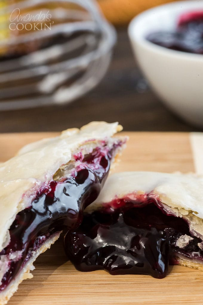 hand pie broken in half with blueberry filling coming out