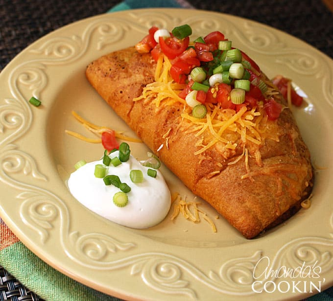 taco empanadas topped with tomatoes and cheese with sour cream