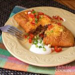 A photo of a taco empanada on a plate cut in half topped with chopped green onions, tomatoes and sour cream.