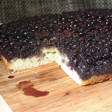 A photo of an easy blueberry upside down cake resting on a wooden cutting board.