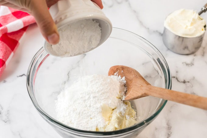 adding powdered sugar to cream cheese in bowl