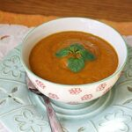 A close up photo of a bowl of pumpkin soup with a spoon on the side.