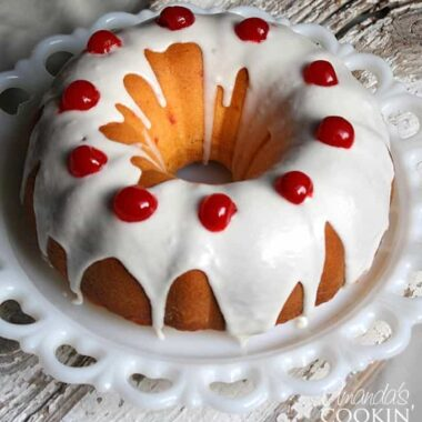 A close up photo of a maraschino cherry Bundt cake on a decorative platter with almond butter glaze and  cherries on top.