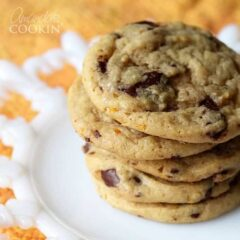 A close up photo a stack of orange chocolate chip cookies.
