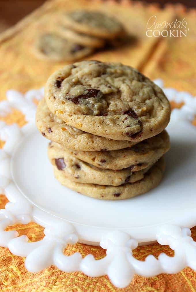 A stack of orange chocolate chip cookies on a white plate.