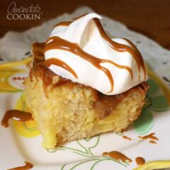 A close up photo of vanilla dream crock pot cake topped with Cool Whip and drizzled Dulce de Leche.