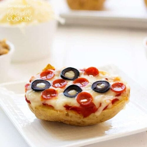 A close up of a baked potato pizza on  white plate topped with pepperoni and black olives.