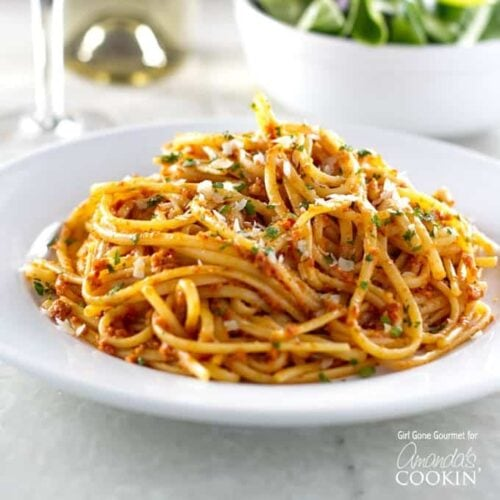 A photo of sun dried tomato pesto on pasta on a white plate.