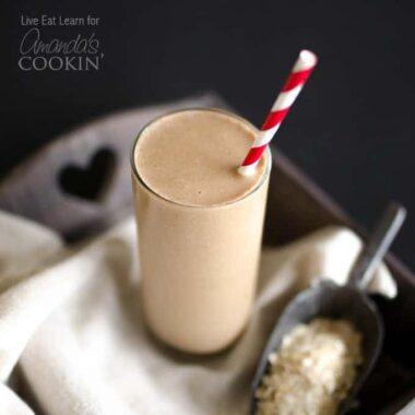 A close up photo of a tall loaded coffee breakfast smoothie served with a red and white straw.