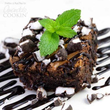 A close up photo of a peppermint patty brownie topped with drizzled chocolate sauce, chopped peppermint patties and a mint leaf.