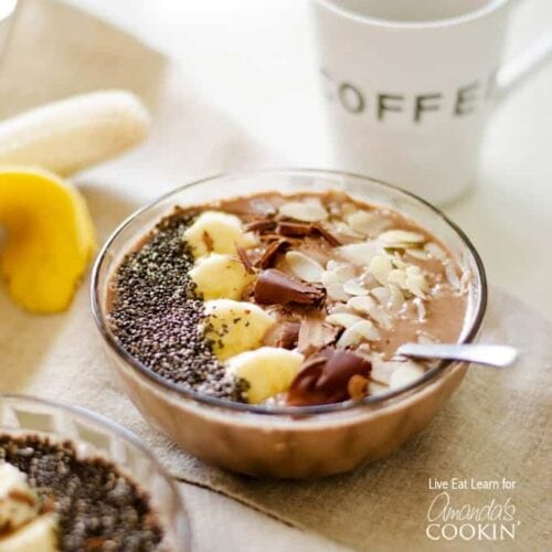 A close up of a mocha smoothie bowl topped with sliced banana, shaved chocolate and sliced almonds.