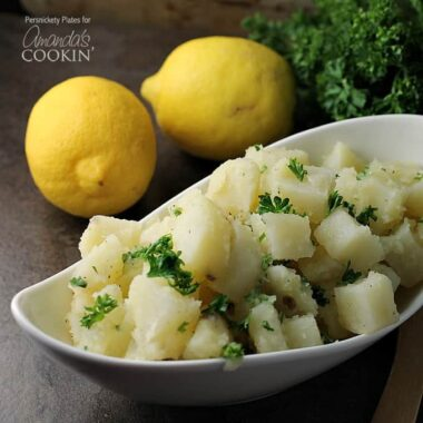 A close up of a long white bowl filled with Mediterranean potato salad and topped with chopped parsley.