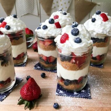 mason jars layered with berries, cake, and whipped cream