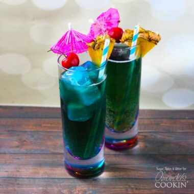 Two tall glasses filled with blue mermaid cocktails and topped with a cherry, pineapple wedge, an umbrella and a straw.