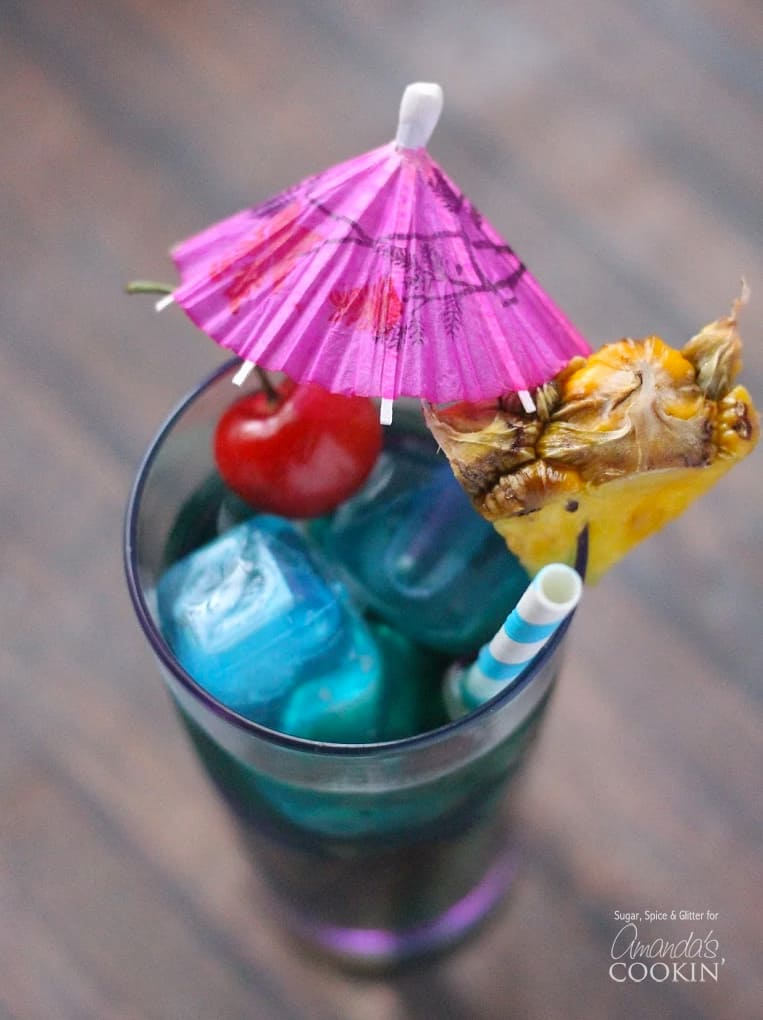 A tall glass filled with a blue mermaid cocktail and topped with a cherry, pineapple wedge, an umbrella and a straw.