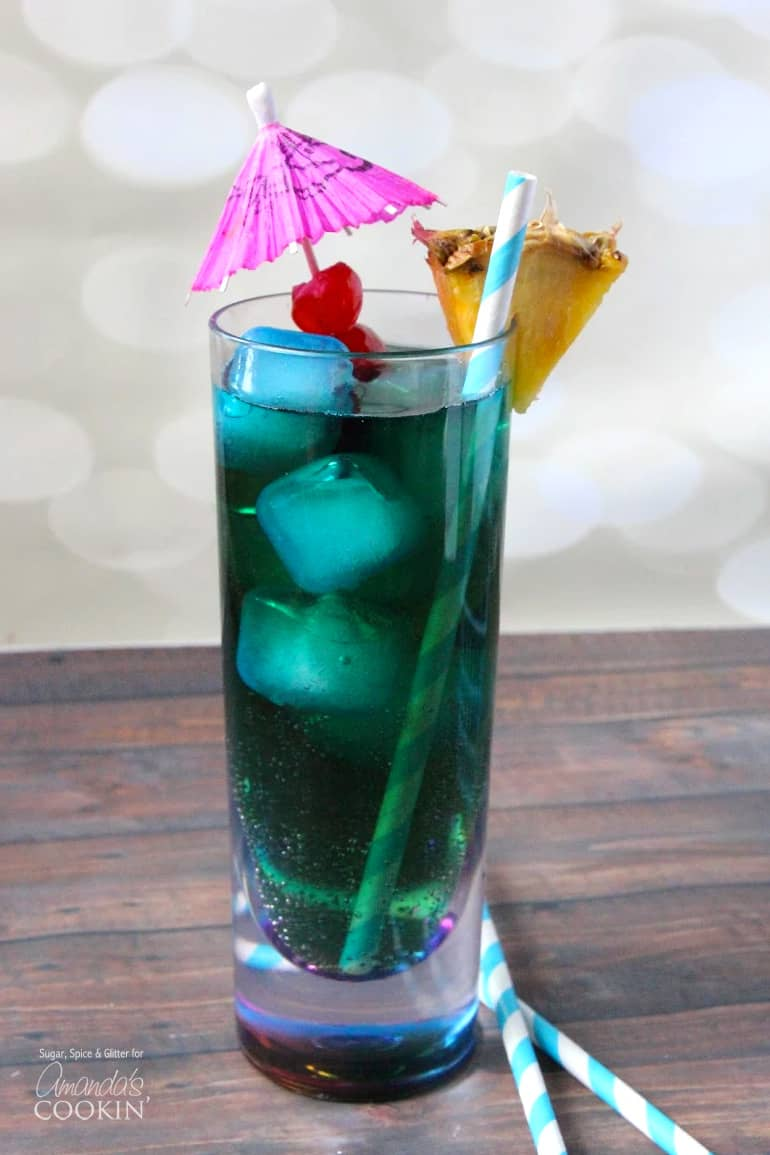 blue cocktail in a tall glass with parasol