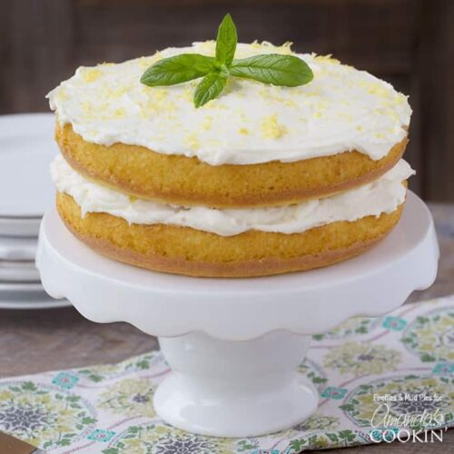 A close up of a lemon curd poke cake on a white cake stand topped with fresh mint leaves.
