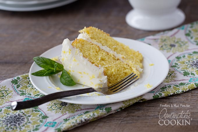 A close up of a slice of lemon curd poke cake on a white plate with fresh mint leaves on the side.