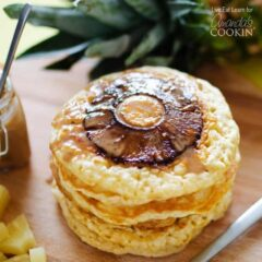 A close up photo of a stack of pineapple pancakes on a wooden cutting board.