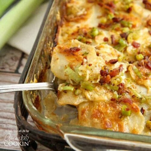 A close up of a spoonful of potatoes au gratin with bacon and leeks.
