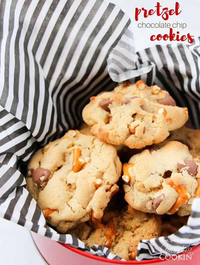 A photo of pretzel chocolate chip cookies in a tin lined with black and white striped tissue paper.