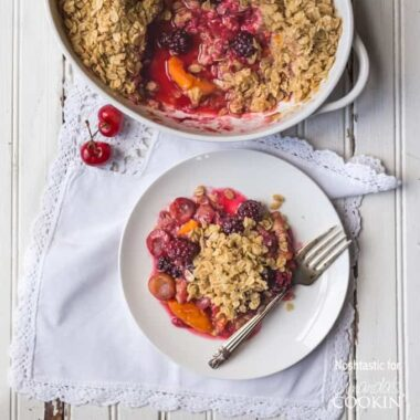 An overhead photo of a serving of summer fruit crisp on a plate with a fork and the entire pan behind it.