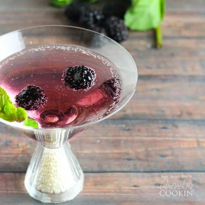 A close up of a blackberry gin martini topped with fresh blackberries and mint leaves.