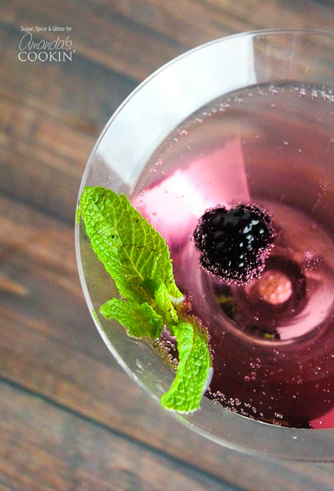 A close up overhead of a blackberry gin martini topped with fresh blackberries and mint leaves.