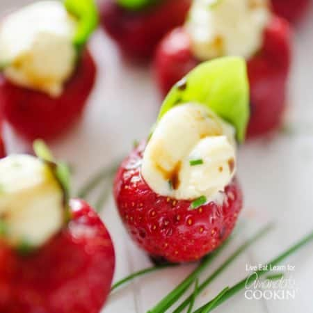 These whipped brie stuffed strawberries are a really quick and healthy appetizer. It's colorful finger food and a snack that your family is going to love.