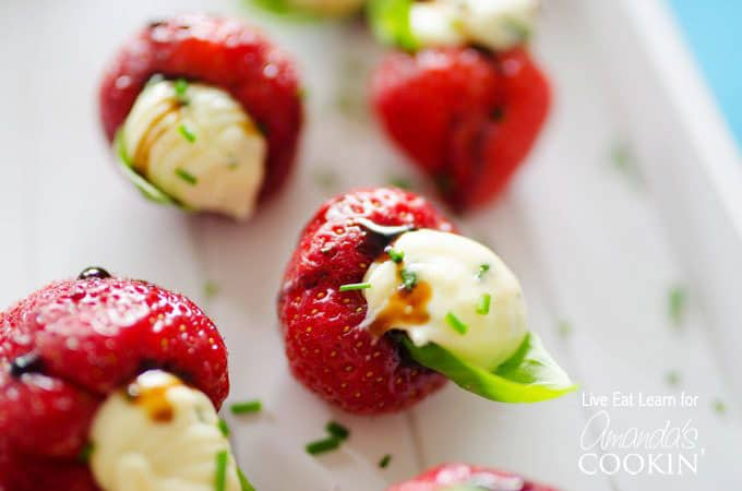 A close up photo of strawberries stuffed with whipped brie and topped with a basil leaf.