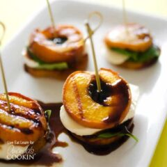 A close up of grilled peach caprese on a white platter.