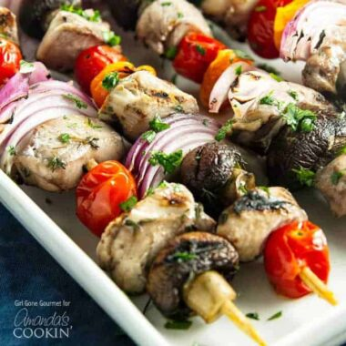 A close up of marinated chicken skewers  with tomatoes, red onions and mushrooms.